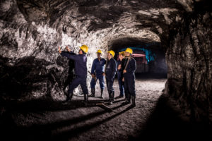 Group of men working at a mine looking at the rock in a dark tunnel- mining concepts